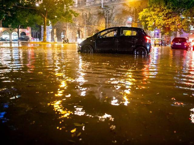 Auto in überfluteter Strasse.