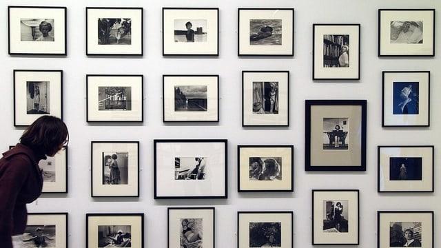 Eine Frau schaut sich im Museum ein Foto an, das mit vielen anderen Bildern an einer Wand hängt.