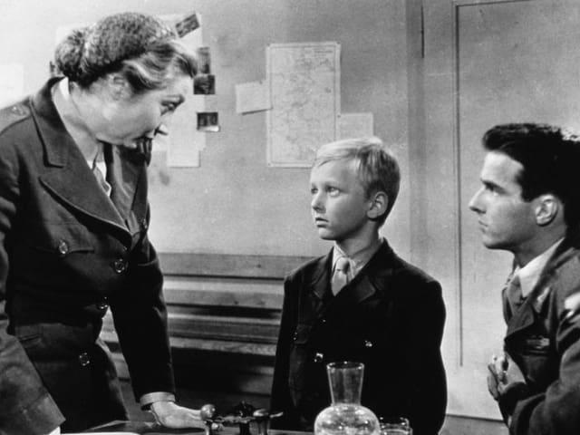 Eine Junge schaut eine Frau in Uniform an.