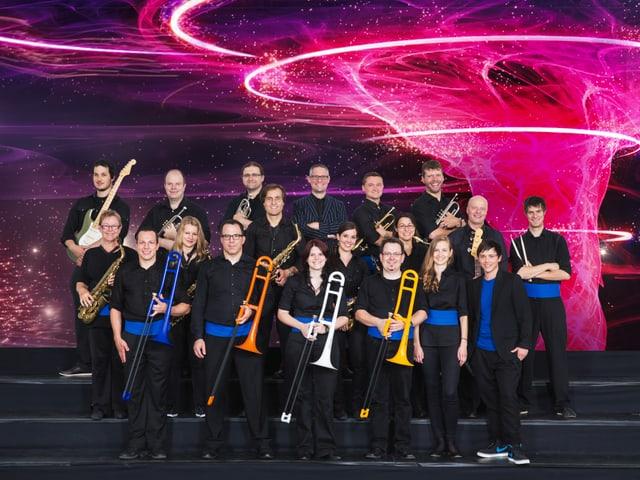 Bigband mit verschiedenen farbigen Posaunen im Gruppenbild