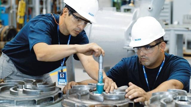 Zwei Männer arbeiten an einem Metallstück.