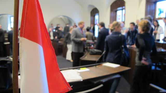 Parlamentarier im Kantonsratssaal in Solothurn am Diskutieren. Im Vordergrund eine Kantonsflagge.