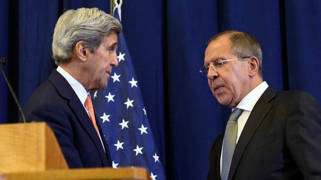 John Kerry e Sergej Lawrow davant in vel blau. Davos John Kerry e vesaivel ina bandiera dals stadis Unids