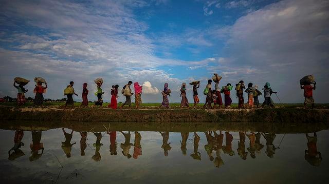 Flüchtlinge auf einem Damm