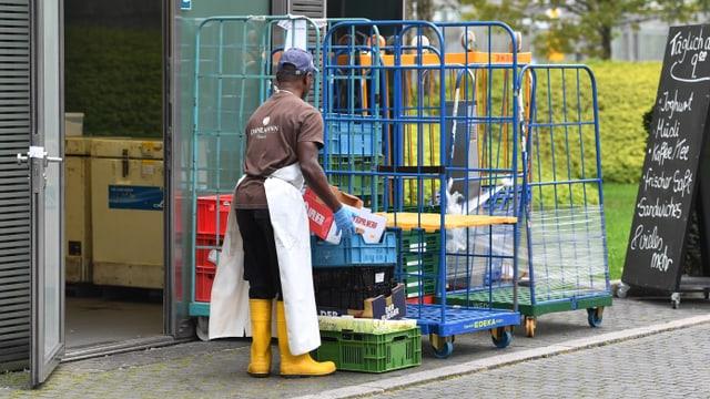 Schwarzer Mann erledigt Aufräumarbeiten im Hinterhof eines Restaurants