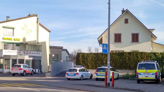 Haus von aussen. Im Vordergrund vier Polizeiautos.