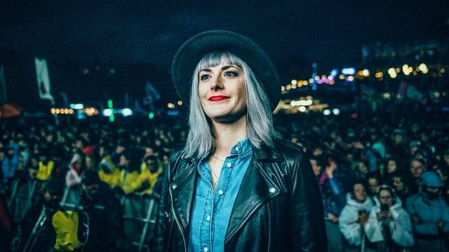 Tina Nägeli mit Hut an einem Festival vor viel Publikum