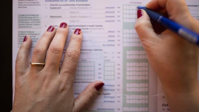 Eine Frau füllt eine Steuererklärung aus.