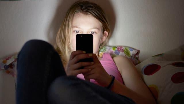 Symbolbild: Mädchen sitzt auf ihrem Bett und surft mit dem Handy.