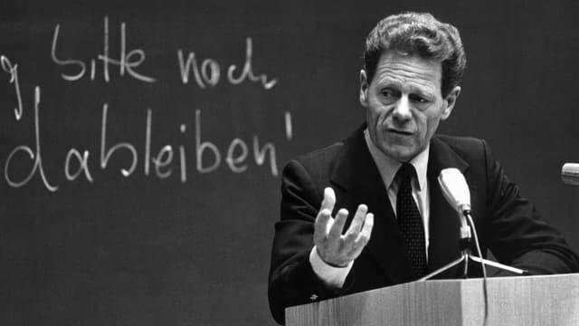 Mann in Anzug und Krawatte steht an einem Rednerpult, auf der Tafel im Hintergrund lässt sich der Schriftzug «Küng, bitte noch dableiben!» erahnen