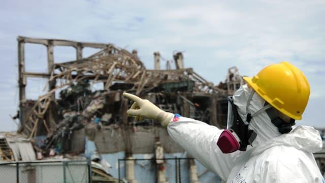 Person mit Schutzanzug- und helm zeigt auf Gebäuderuine