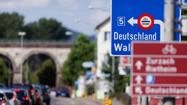 Grenze in Koblenz. Blaues Strassenschild weist den Weg zum Zoll.