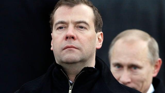 Putin steht hinter grimmig dreinblickendem Medwedew.