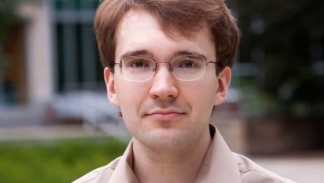Ein junger Mann mit Roten Haaren und Brille.