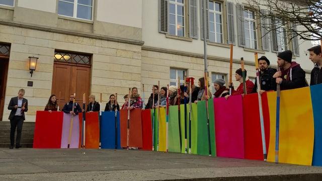 Demonstranten mit farbigen Plakaten vor dem Aargauer Parlamentsgebäude
