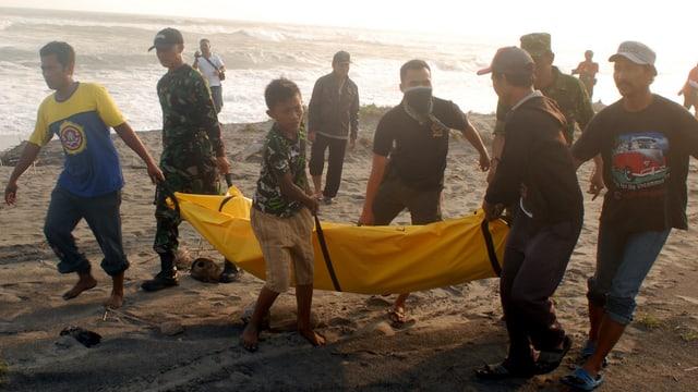Retter tragen am Strand ein Opfer weg