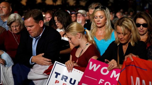 Eine Gruppe Frauen und Männer hält Trum Schilder und betet.