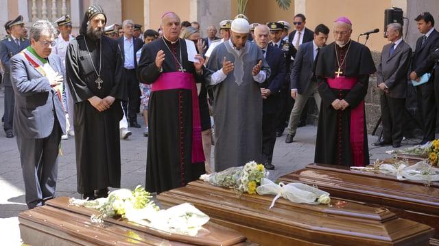 Ein römisch-katholischer Pfarrer, ein Pope und ein Imam segnen die Särge.