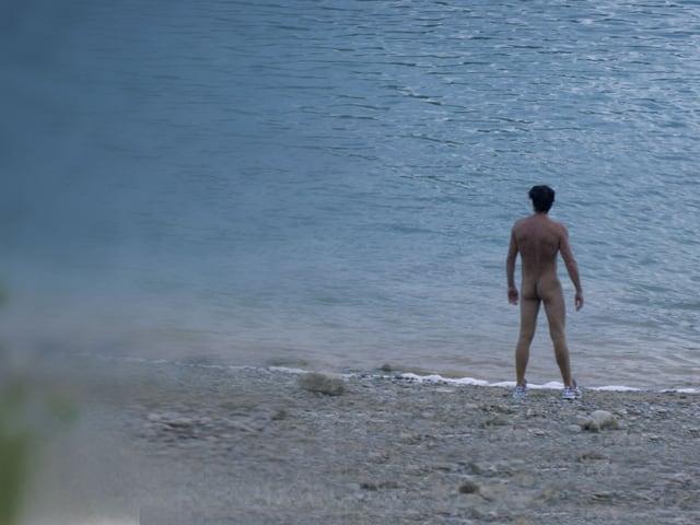 Nackter Mann am See aus der Ferne.