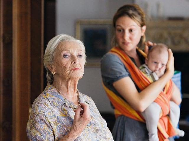 Eine ältere Frau, dahinter eine junge frau mit Baby im Tragetuch.