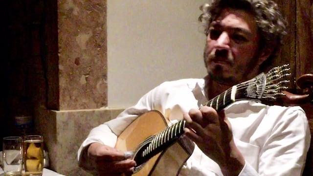 Ein Mann im weissen Hemd spielt Gitarre.