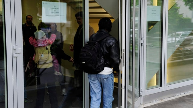 Ein Mann öffnet eine Glastür.