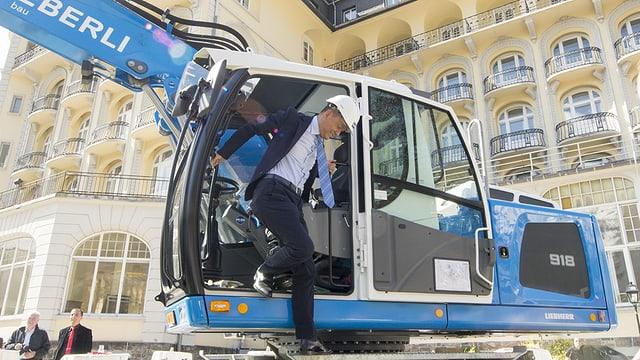 Ein Bagger vor einem grossen Hotelkomplex daraus steigt ein Mann mit Bauhelm aus.