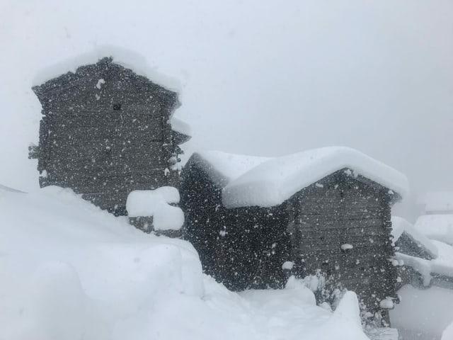 Verschneite Häuser in einem Bergdorf.