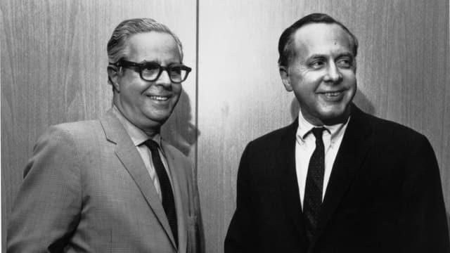 Zwei Männer stehen nebeineinander und lachen.