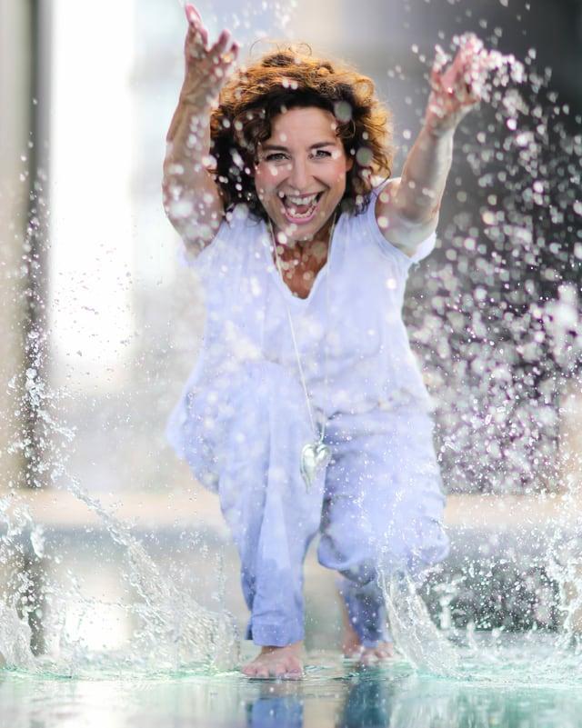 Varell  steht in Pfütze und spritzt Wasser mit den Händen in Richtung Kamera.