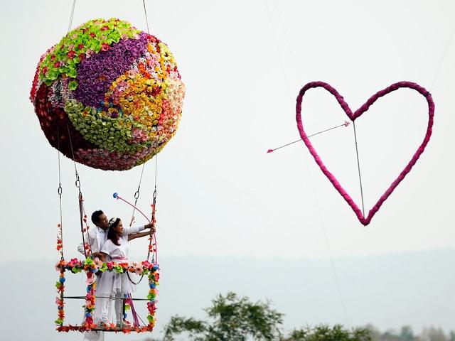 Ein Paar in luftiger Höhe zielt mit Pfeil und einem Bogen auf ein Herz