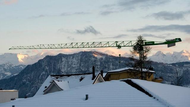 Kran über Hausdach mit Bergen im Hintergrund.