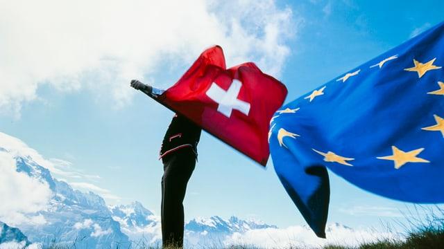 Symbolbild: Ein Fahnenschwinger schwingt eine Schweizer Fahne, ebenfalls im Bild, eine EU-Fahne.