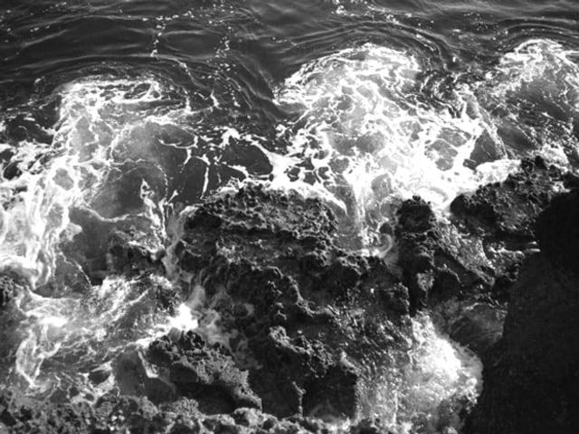 Sprudelndes Meerwasser und Küstenfelsen.