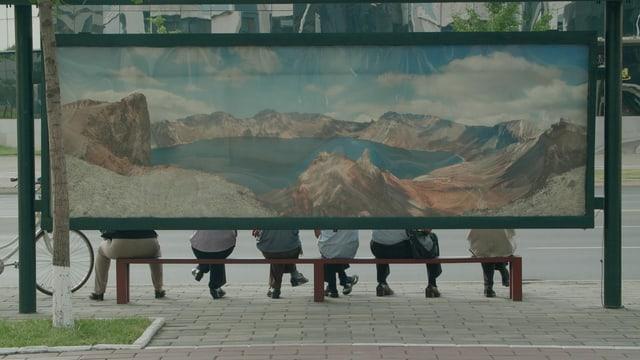 Bushaltestelle von hinten. Fünf Menschen sitzen auf einer Bank. Hinter ihnen ein grosses Gemälde einer Berglandschaft