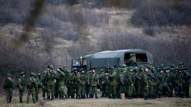 Mehrere Dutzend bewaffnete Soldaten in grünen Uniformen sammeln sich in der Ferne um einen Truppentransporter.