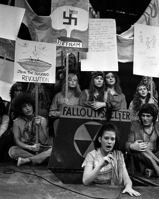 Junge Frauen auf der Bühne mit Protestplakaten.