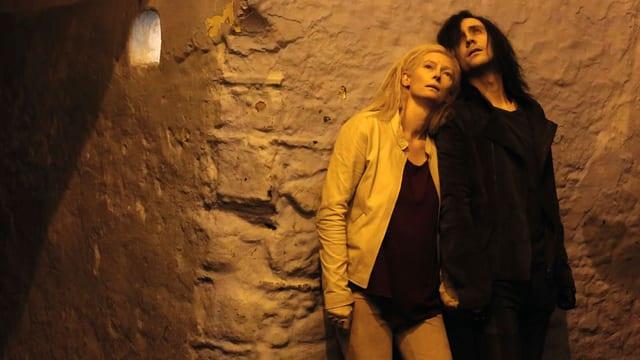 Tilda Swinton als Eve und Tom Hiddleston als Adam, zusammen an einer gruftartigen Wand gelehnt, nach oben blickend.