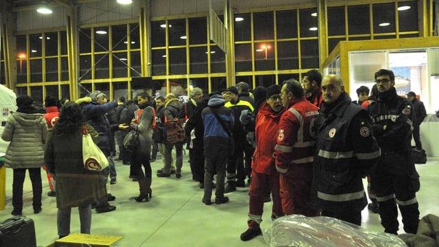 Menschen und Rettungskräfte warten am Hafen von Brindisi