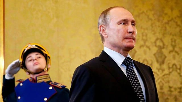 Wladimir Putin, hinter ihm ein junger Soldat, der ihm salutiert.
