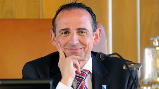 Ein Mann sitzt hinter einem Mikrofon und lächelt