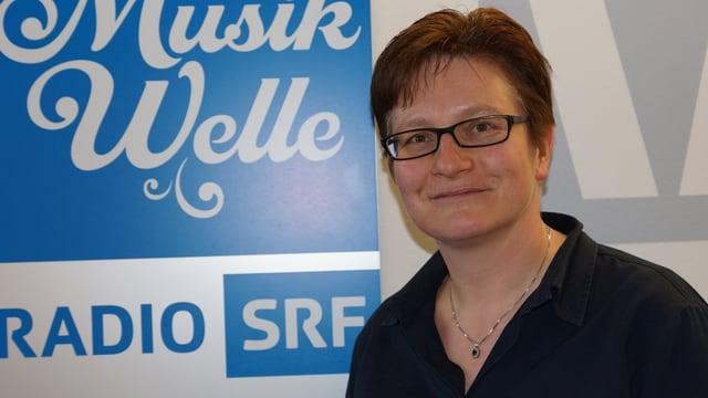 Die Komponistin hat kurze dunkle Haare, trägt eine Brille und steht vom dem SRF Musikwelle-Logo.