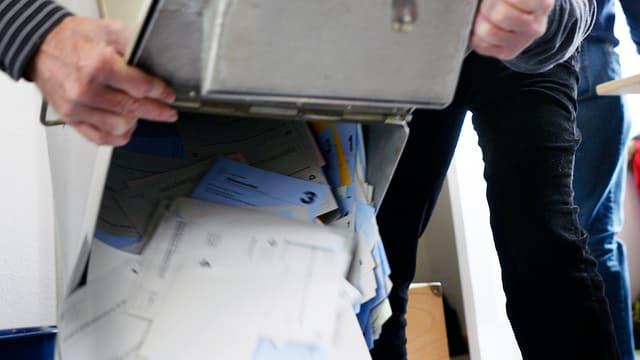 Eine Urne mit Stimmzetteln wird ausgeleert.