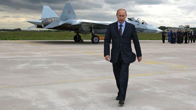 Putin auf einem Militärstützpunkt, hinter ihm ein stehendes Kampfflugzeug und eine Gruppe Leute.