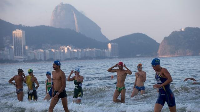Triathleten steigen an der Copacabana aus dem Wasser