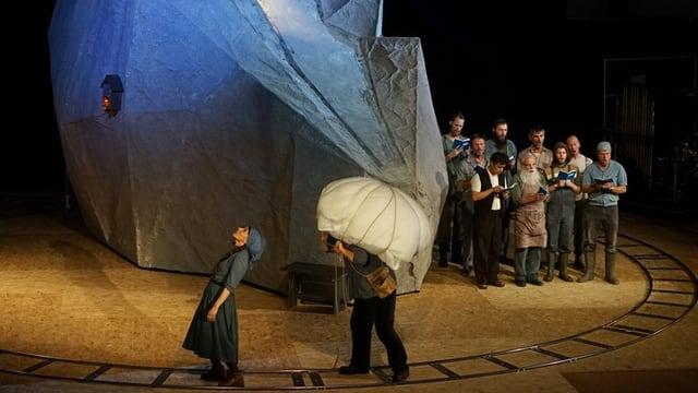 Blick auf die Hauptbühne des Theaters Basel mit einem Berg als Bühnenbild, zwei Schauspielern und einem Theaterchor
