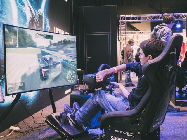 Ein Gamer hat im Rennsessel Platz genommen und heizt über die Rennstrecke