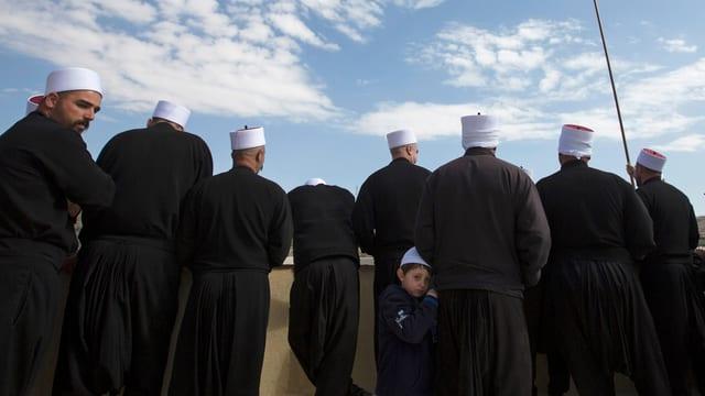 Eine Gruppe drusischer Männer mit typischen, traditionellen weissen Kopfbedeckungen von hinten.