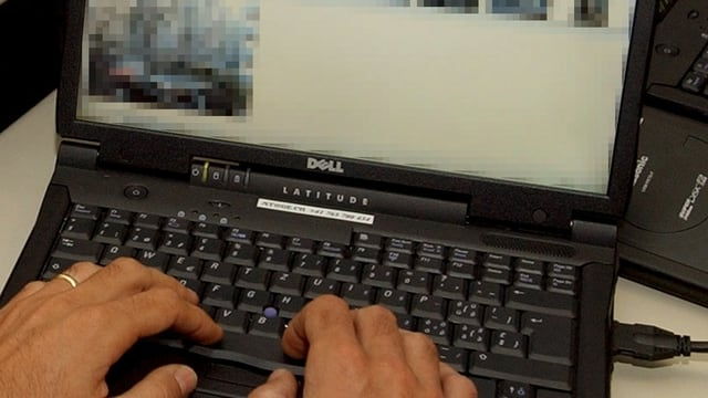 Ein Fahnder sichtet Bilder am Computer.