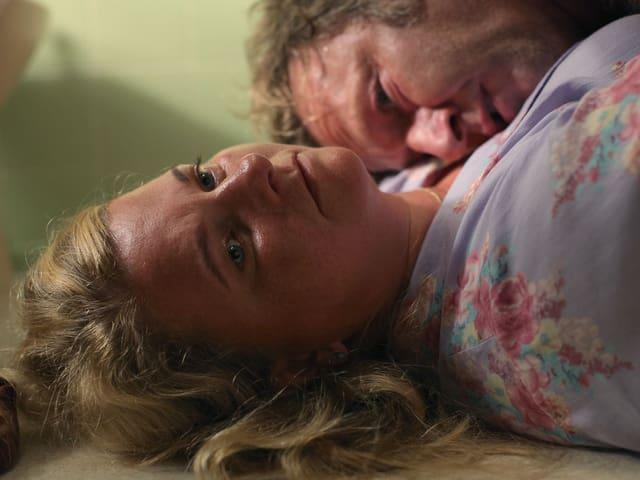 Eine Frau liegt am Boden oder auf einem Bett. Sie blickt nach oben, mit einem unfokussierten Blick. Ein Mann liegt auf ihr.